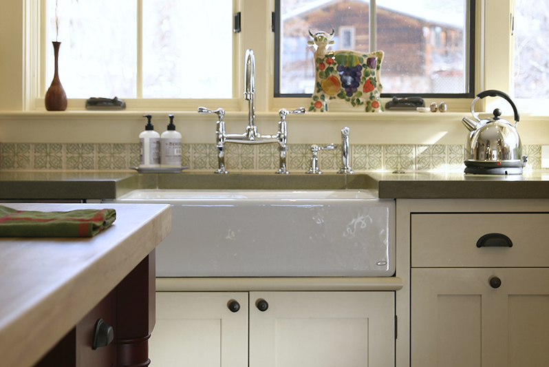 Kitchen with concrete countertop, farmhouse sinkn and bridge faucet.